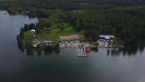 Aerial view over wooden Pier in blue lake. Small Dock and Boat at the lake. Pier with boats. Aerial view stock footage