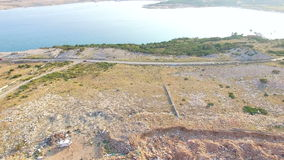 Aerial view of Pag island's scrapyard with sea in the background, Croatia stock footage