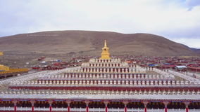Aerial view of the pagodas with buddhist monks walking under. At Yarchen Gar Monastery In Sichuan, China stock video