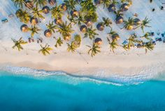 Aerial view of palms on the sandy beach of Indian Ocean at sunset. Aerial view of umbrellas, palms on the sandy beach of Indian Ocean at sunset. Summer holiday stock photo