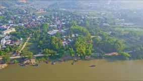 Aerial View Panorama of Town on Quiet River Bank. Aerial view panorama of beautiful town with roads on green quiet river bank with fishing boats stock video footage
