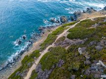 Aerial view of the panoramic path that leads to the bloody islands. Corsica, France. Aerial view of the panoramic path that leads to the promontory view point to stock photography