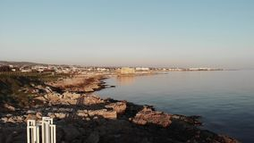 Aerial view of Paphos City with white monument on rocky beach during sunset. Cyprus nature.  stock video footage
