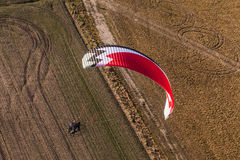 Aerial view of paramotor flying over the harvest field Stock Image