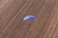 Aerial view of paramotor flying over the harvest field Royalty Free Stock Photos