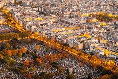 Aerial view of Paris in autumn from the Montparnasse Tower with cemetery versus traffic and buildings. Royalty Free Stock Images
