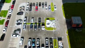 Aerial view of parking with many cars near green lawn. Motion. Top view of parking area with concrete pavement on a