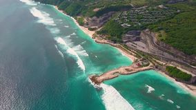 Aerial view of part island with turquoise ocean waves, villas on cliff in green. Aerial view of beach with turquoise ocean waves, road and villas on cliff in stock video footage
