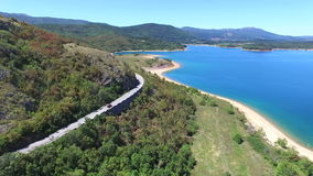 Aerial view of paved road passing artificial lake of Peruca, Croatia. Aerial view of paved road through mountains passing artificial lake of Peruca, Croatia stock video footage