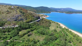 Aerial view of paved road passing artificial lake of Peruca, Croatia. Aerial view of paved road through mountains passing artificial lake of Peruca, Croatia stock footage