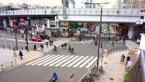 Aerial View of Pedestrians Crossing Crosswalk Cars Traffic in Japan. OSAKA, JAPAN - MARCH 2015: Aerial View of Pedestrians Crossing Crosswalk Cars Traffic in stock footage