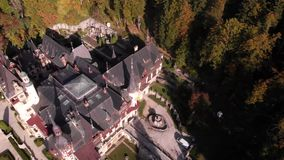 Aerial view of Peles Castle in Sinaia. Carpathian mountains, Brasov region, Romania. Beautiful autumn landscape in castle surrounded with the forest and high