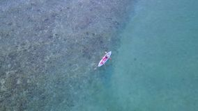 Aerial view of people canoeing on the sea. Beautiful aerial view footage of happy family canoeing together on the sea in Labuan Bajo, East Nusa Tenggara close to stock footage