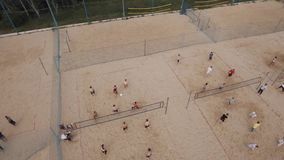 Aerial view people compete beach volleyball at sand sports ground on sunny day stock footage