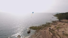 Aerial view people fly kites on sandy sea shore with white tents in summertime stock video footage