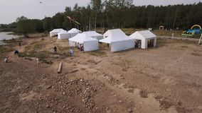 Aerial view people fly kites on wild sea shore with white tents in summertime stock video