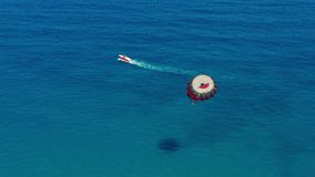 Aerial view. People flying on a colorful parachute towed by a motor boat. Parasailing in blue sky. Aerial view. People flying on a colorful parachute towed by a stock footage