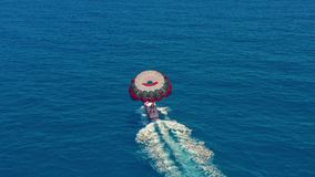 Aerial view. People flying on a colorful parachute towed by a motor boat. Parasailing in blue sky. stock video