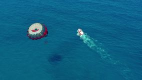 Aerial view. People flying on a colorful parachute towed by a motor boat. Parasailing in blue sky. Aerial view. People flying on a colorful parachute towed by a stock video