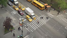 Aerial view of people move across crosswalk of city intersection stock video