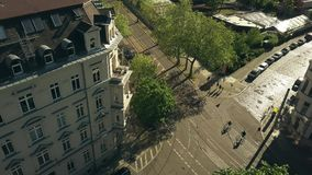 Aerial view of people riding bikes along sunny street in Leipzig, Germany. Aerial view of people riding bicycles along sunny street Stock Images
