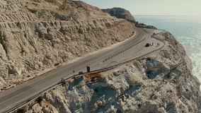 Aerial view on the people on the road on the rock. Beautiful view on the road on the rock and blue ocean near it. The camera is moving on the three people and stock video footage