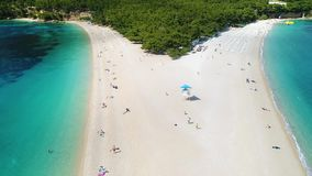 Aerial view of people swimming and sunbathing on sandy beach. Aerial view of Zlatni Rat, a sandy beach on the island of Brac, Croatia stock video