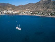 Aerial view photo of Luxury vintage two masted tourist trip ship stays on anchor in the bay, calm transparent water of stock photo