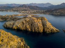 Aerial view of the Pietra Lighthouse and the Genoese tower at sunset. Red Island, Corsica, France. Aerial view of the Pietra Lighthouse at sunset and the Genoese royalty free stock photos