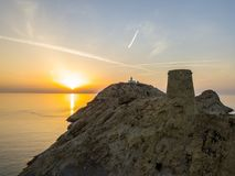 Aerial view of the Pietra Lighthouse at sunset and the Genoese tower at sunset. Red Island, Corsica, France Royalty Free Stock Image