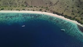 Aerial view of Pink Beach in Komodo Island. Beautiful aerial view footage of Pink Beach with boats, turquoise sea water, and pink sand in Komodo National Park stock video