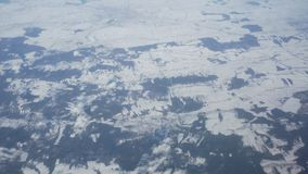 Aerial view from the plane on snowy winter fields and clouds stock video