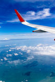 Air Travel. Theme: Airplane Wing against a Vivid Blue Sky and Ocean Stock Photos