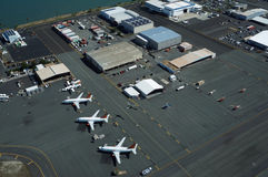 Aerial view of planes, helicopters, and cars parked by buildings Stock Photo