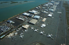 Aerial view of planes, helicopters, and cars parked by buildings Stock Image