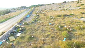 Aerial view of plastic bags lying in grass by road, Pag island, Croatia. Aerial view of plastic bags lying in grass by asphalted road, Pag island, Croatia stock video