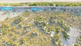 Aerial view of plastic bags lying in grass by road, Pag island, Croatia. Aerial view of plastic bags lying in grass by asphalted road, Pag island, Croatia stock video footage