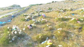 Aerial view of plastic bags lying in grass by road, Pag island, Croatia. Aerial view of plastic bags lying in grass by asphalted road, Pag island, Croatia stock footage