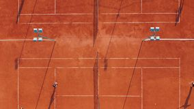 Aerial view. Players are playing tennis on orange court. stock footage