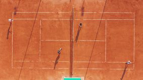 Aerial view. Players are playing tennis on orange court. stock video