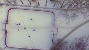 Aerial view on playing football in the snow. Stock. Aerial view of soccer field in winter with snow. A small town, trees
