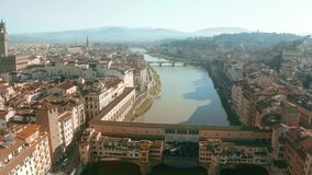 Picturesque aerial view of Ponte Vecchio bridge and Arno river within cityscape of Florence, Italy. Aerial view of Ponte Vecchio bridge and Arno river within stock video footage