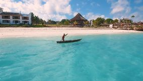 Aerial view of a poor fisherman sails on a small boat along a tropical beach. Aerial view of a poor fisherman with a torn shirt sails on a small boat on clear stock video