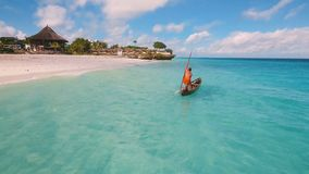 Aerial view of a poor fisherman sails on a small boat along a tropical beach. stock video footage