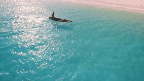 Aerial view of a poor fisherman sails on a small boat along a tropical beach. Aerial view of a poor fisherman with a torn shirt sails on a small boat on clear stock footage