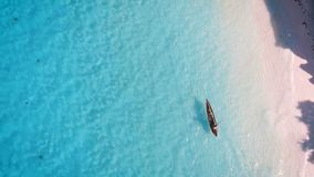 Aerial view of a poor fisherman sails on a small boat along a tropical beach. stock video