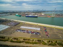 Aerial view of Port Melbourne with moored cargo vessels, imported cars parking lots, and Melbourne CBD skyline on the horizon. Aerial view of Port Melbourne stock photos