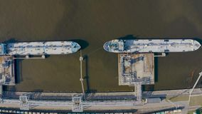 Aerial view port with railway infrastructure for the delivery of bulk cargo by sea, loading oil using a pump station in ship tanke