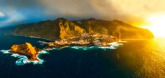 Aerial view of Porto Moniz at sunset with warm sun light and storm clouds gathering. Sunset light and rain clouds over Porto Moniz, Madeira, Portugal royalty free stock image