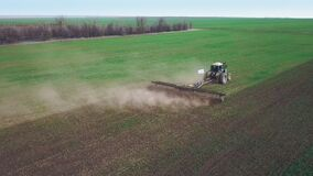 Aerial view of a powerful energy-saturated tractor with a large hook force, performing tillage for sowing winter crops